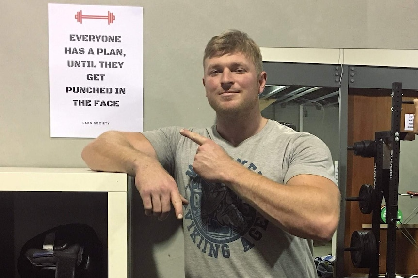 A man leans on a shelf and points to a sign at the Lads Society clubhouse