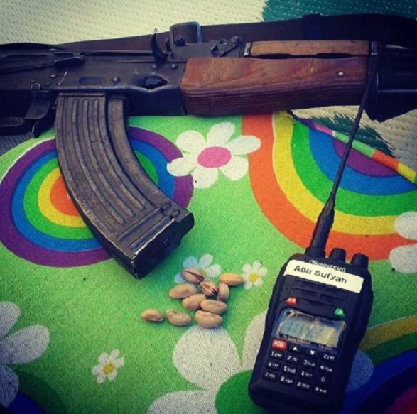 A machine gun, pistachios and a walkie talkie sit on a table covered with a bright rainbow.