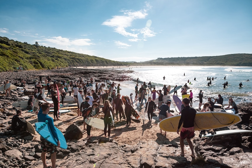 Surfers walk to the water to participate in a paddle-out.