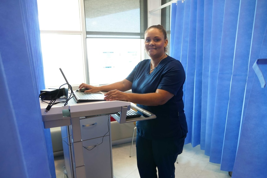 A woman stands in front of a computer in a room surrounded by blue medical curtains.