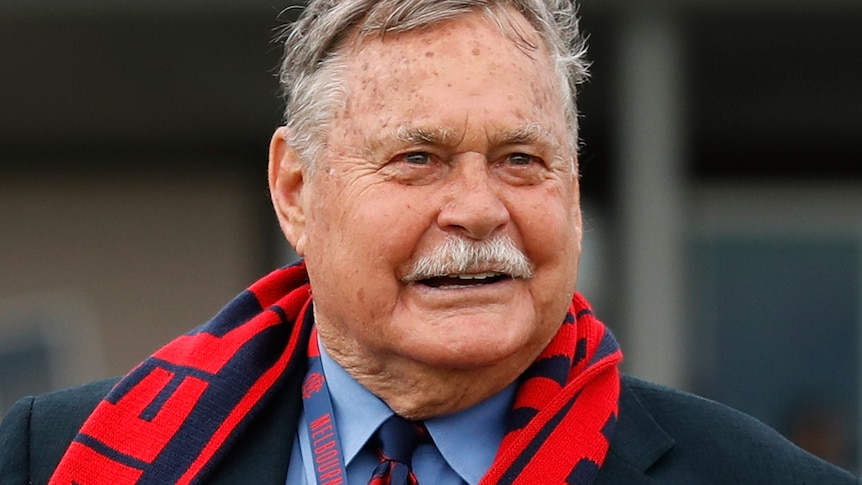Ron Barassi smiles wearing a suit and a Melbourne Football Club scarf and lanyard