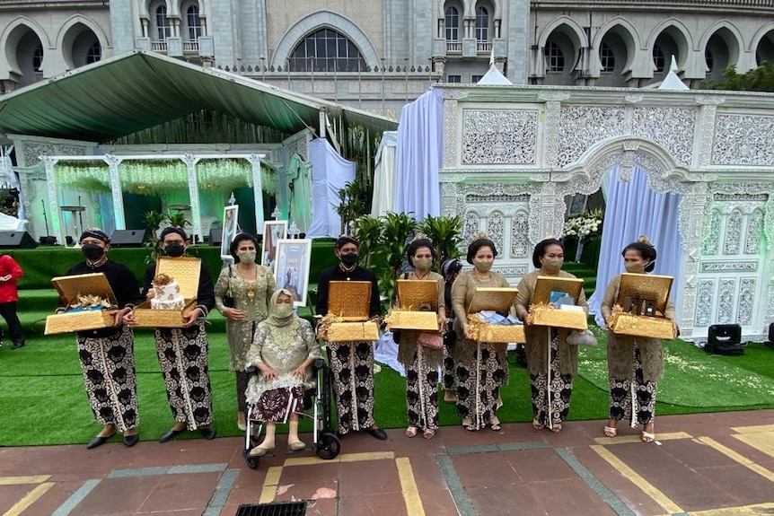 Nine people from the wedding party stand in a row with boxes, wearing masks.
