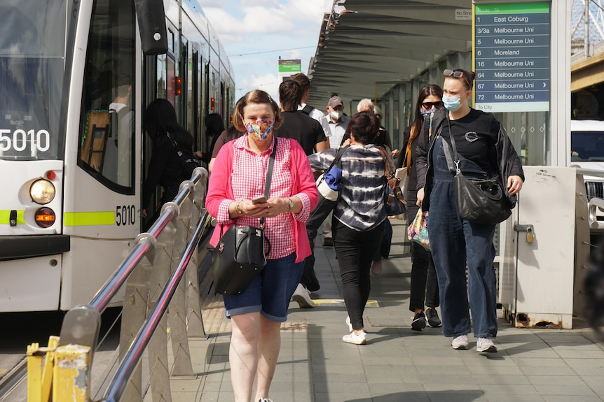 Commuters wear face masks as they walk off a Melbourne tram on a sunny day.
