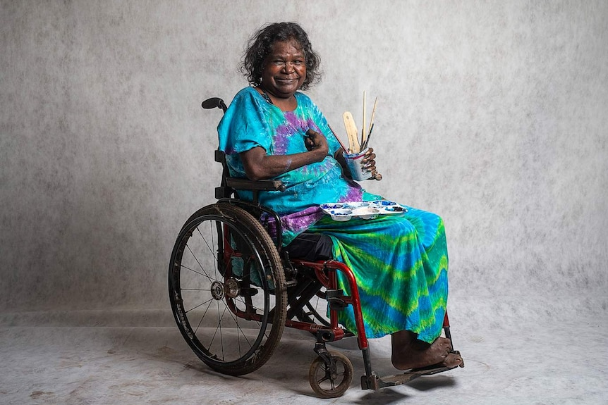 The artist Dhambit Mununggurr in bright tie-dyed top and skirt, sitting in wheelchair smiling, holding jar with brushes.