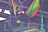 Protester sitting in a hammock under a bridge with a duffle bag