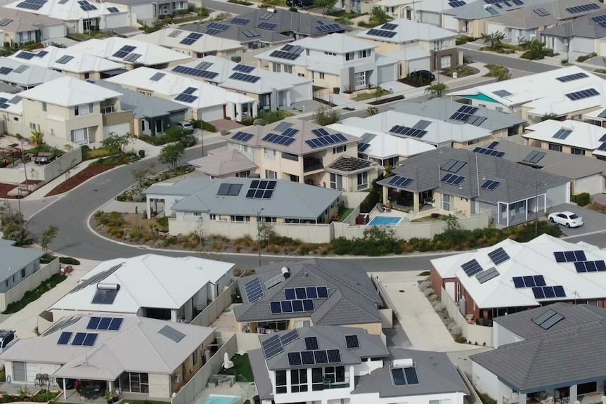 An aerial view of a suburb, many of whose houses have solar panels.