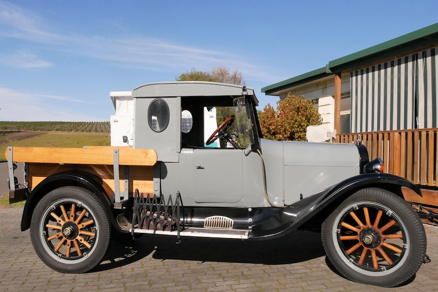 A grey, restored vehicle from the 1920s with wooden spoke wheels and a wooden ute tray top is parked in a driveway.