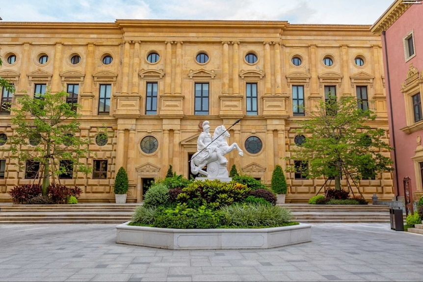 A classical european building with a statue of a man riding a horse.