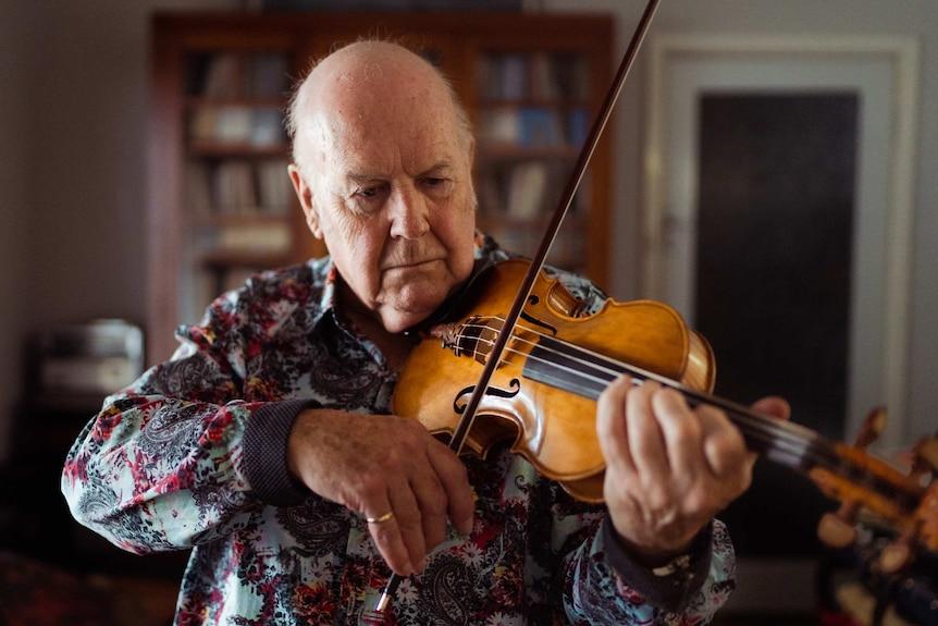 A bald man wearing a dark floral shirt playing a violin