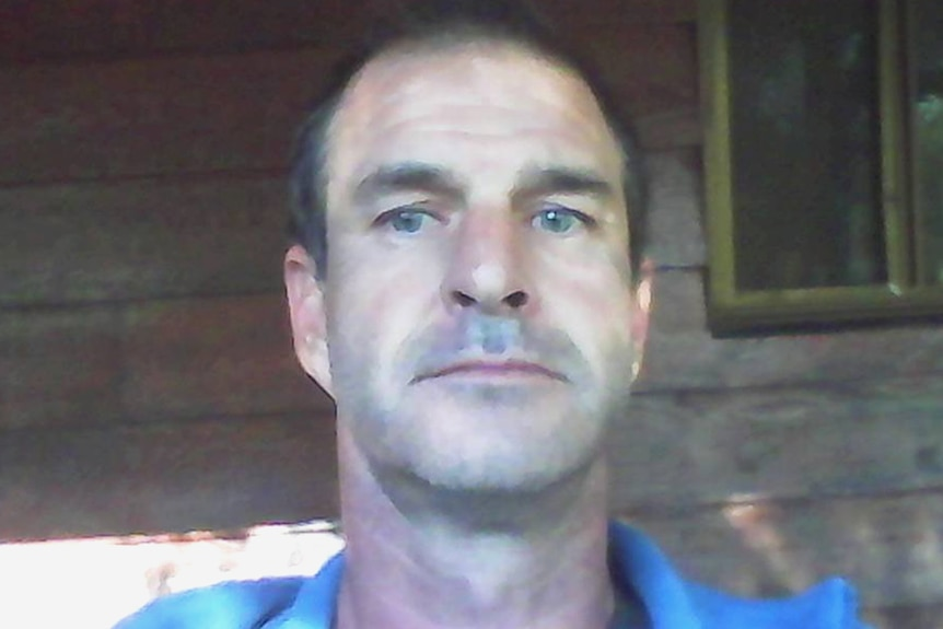 The face of a man standing in front of an old wooden house