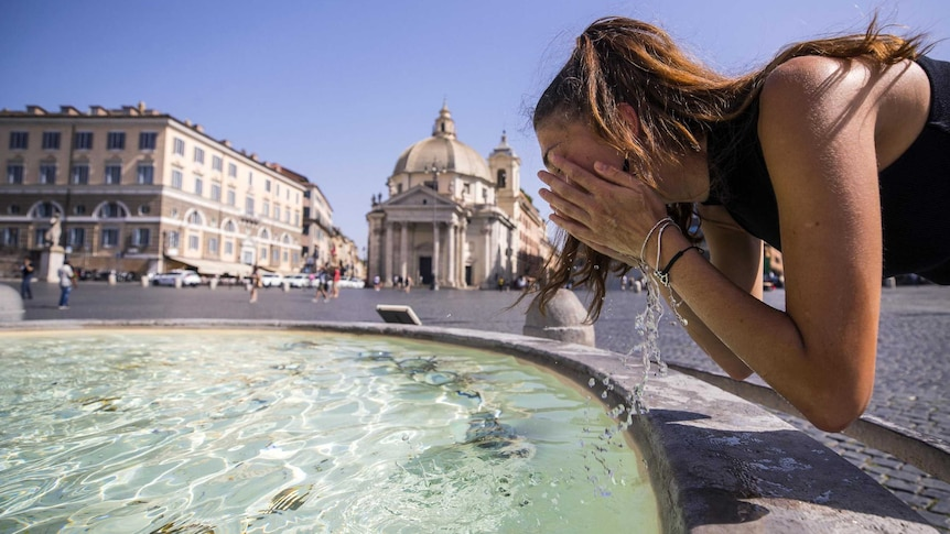 A woman cools off in a fountain at Piazza del Popolo in Rome,Italy. Old buildings can be seen on the far side of the piazza.