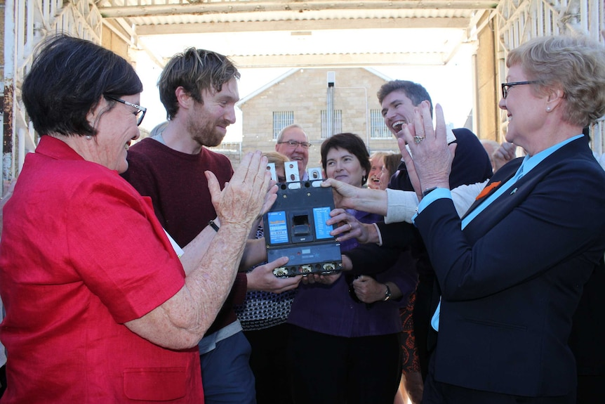 A group of smiling people hold a renewable energy device