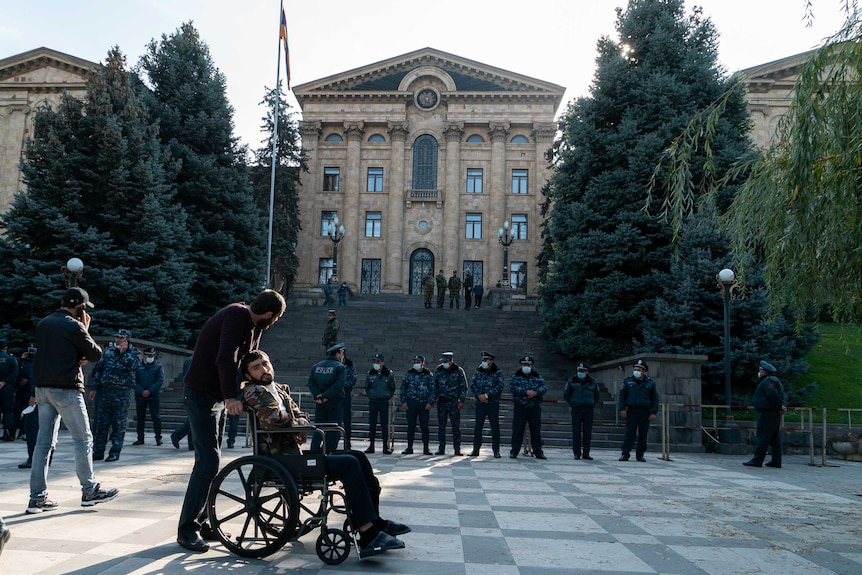 A soldier in a wheelchair sits outside an official building with a line of police in front of him.