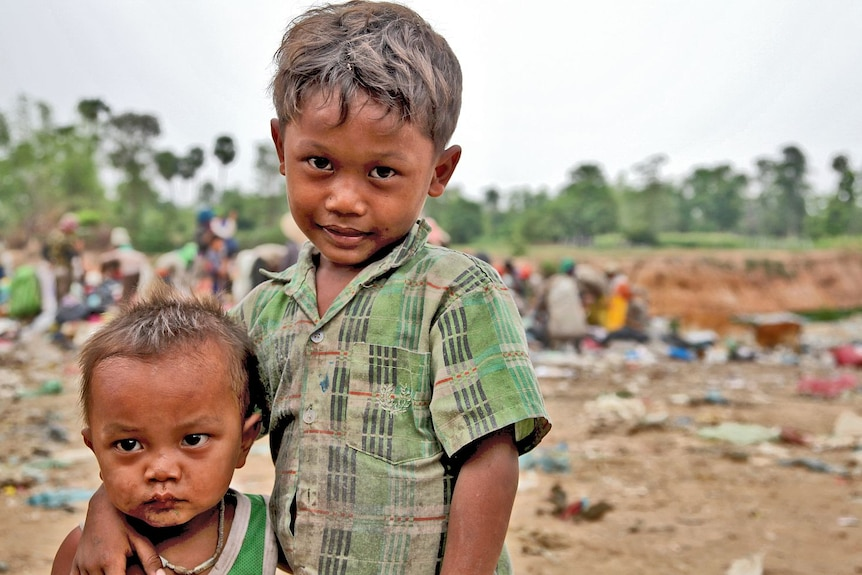 Young boys embrace at a Cambodian rubbish dump