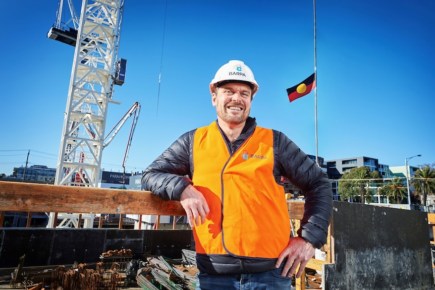 A man in a high-vis vest and hard hat with Aboriginal flag behind him.