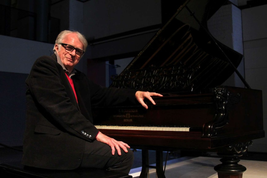 A man sits at a piano and smiles for the camera.