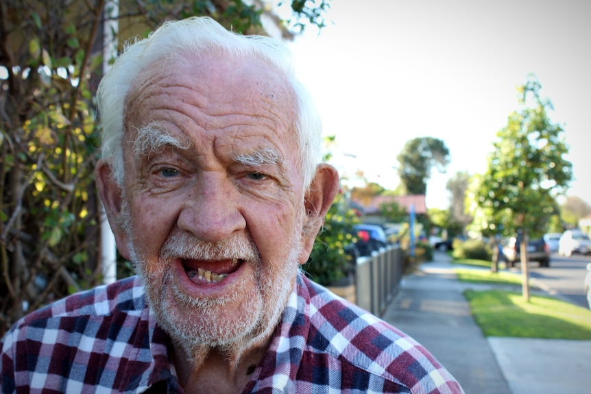 A close up of an elderly man with a checked shirt standing on a suburban street.
