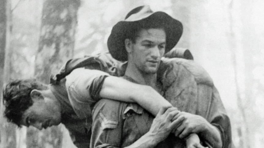 Black and white photo of Leslie 'Bull' Allen carrying wounded soldier