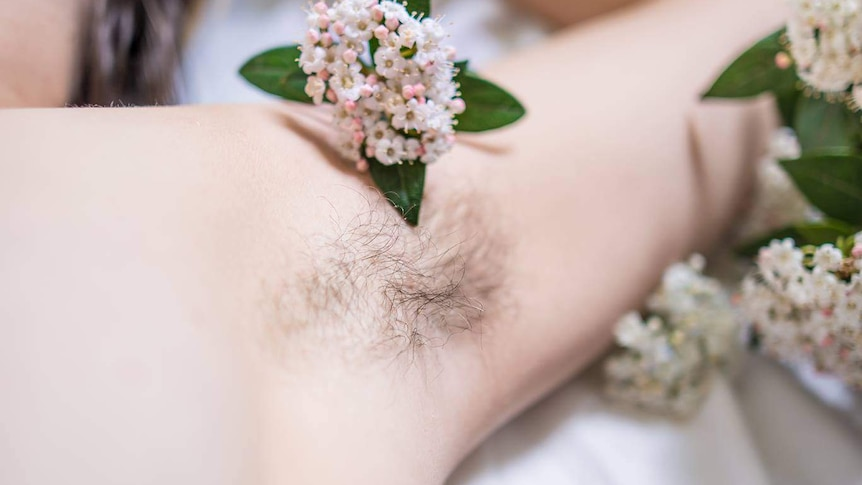 A woman's armpit with her hair grown out, and flowers scattered around.