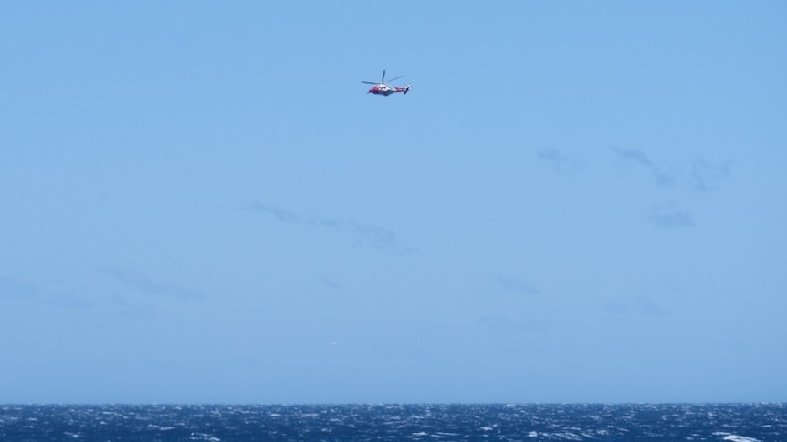 a rescue helicopter in a blue sky and choppy ocean