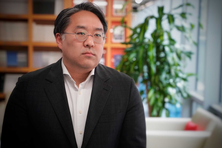 A Korean man in wire rimmed glasses looking solemn