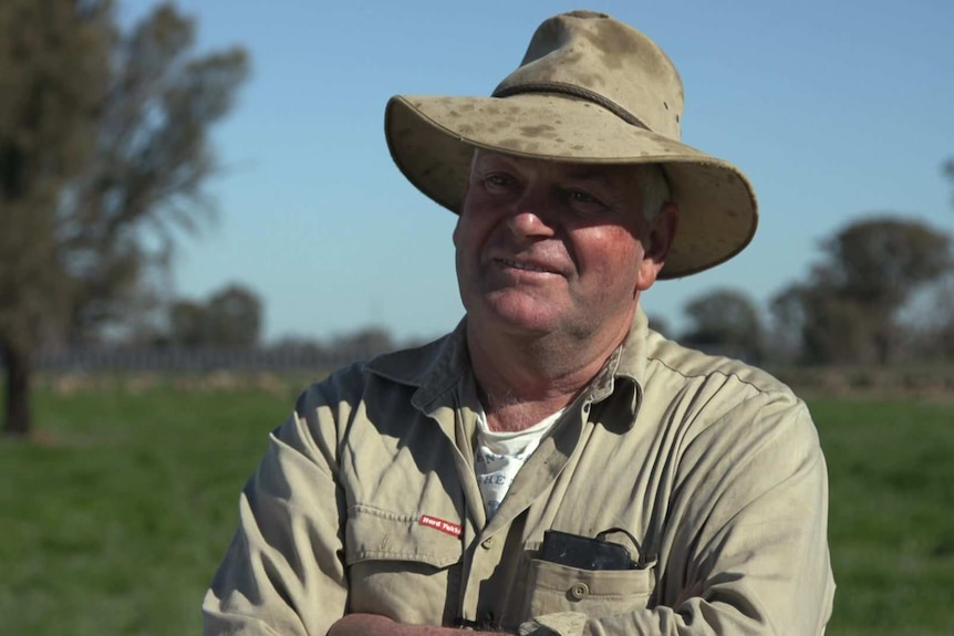 Head shot of farmer Eddie Rovers standing with arms folded in a paddock with sheep and solar panels in the background