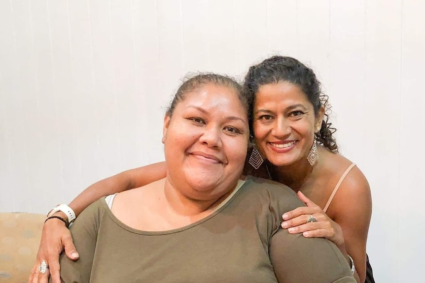 A woman sitting and another woman smiling and wrapping her arms around her.