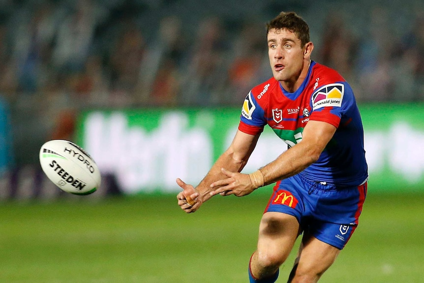 Andrew McCullough passes the ball during an NRL game with the Newcastle Knights.