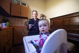 Toddler in high chair looking at camera, mother in background holding spoon and smiling