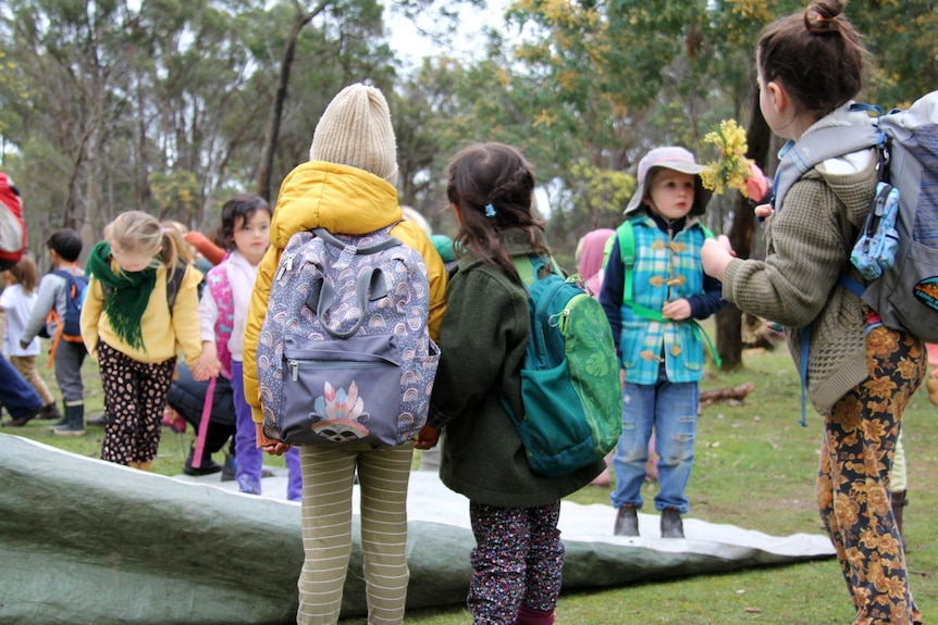 School aged children wearing backpacks as they explore an outside setting, surrounded by tall trees.