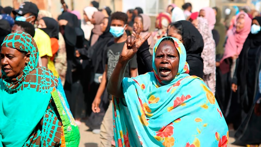 A woman in Sudan in a headscarf flashing a peace sign.