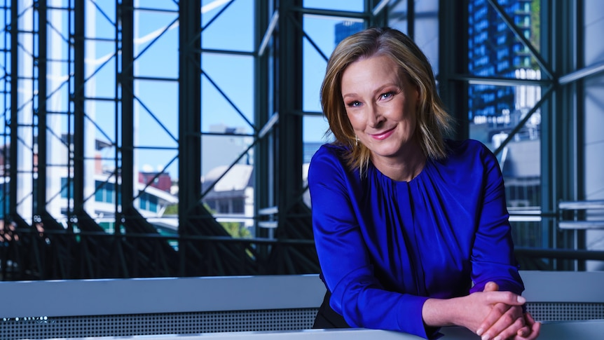 Leigh Sales in a blue sweater, smiling as she leans on a railing