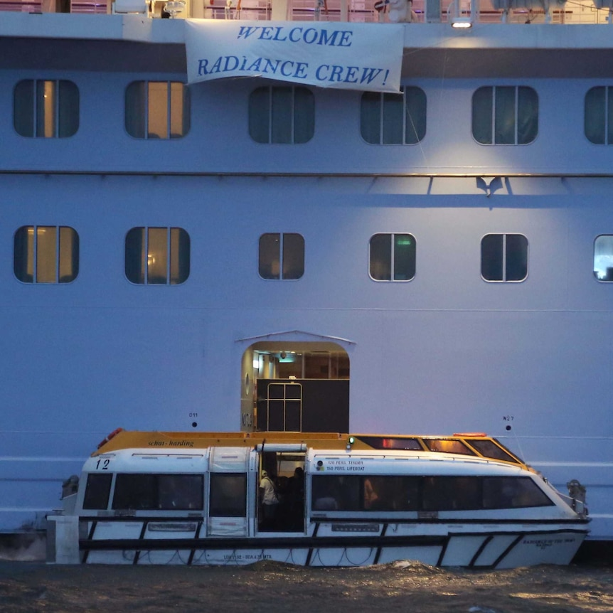 A tender boat sits alongside a cruise ship with a banner reading 'Welcome Radiance Crew!'
