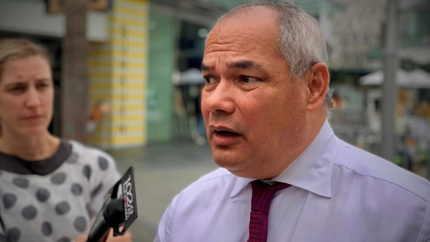 A man in a blue shirt and tie talks into a microphone at an outdoor press conference.
