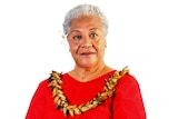 Fiame Naomi Mata'afa poses for a portrait with a red dress, flower in her hair an traditional garland.