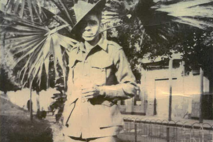 Douglas Love stands with a slouch hat and army uniform.