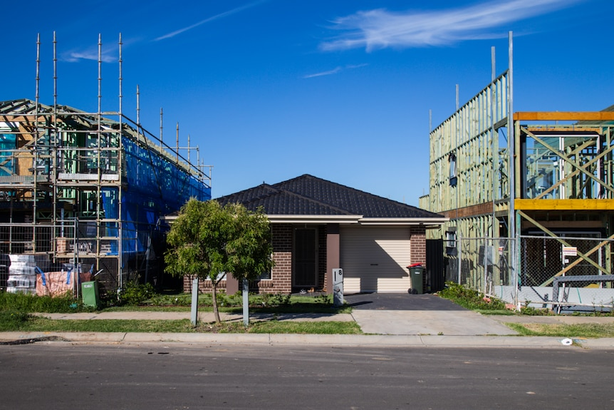 A new, single-storey home sits between two two-storey homes under construction.