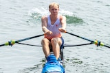 a man rowing in a netherlands team kit. he looks like he is exerting himself