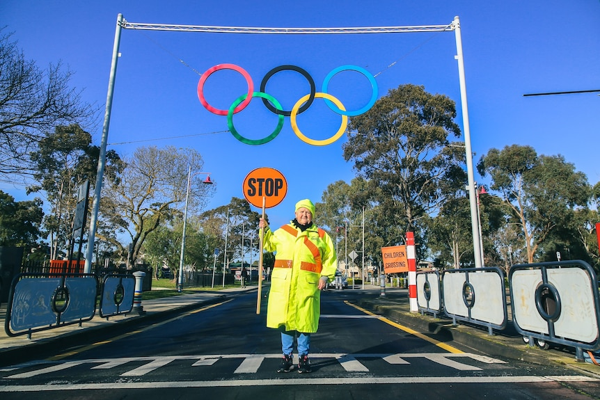 A woman holding a stop sign stands on a pedestrian crossing under Olympic rings.