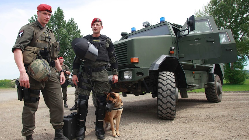 Two men in military gear stand with a dog in front of an army vehicle.