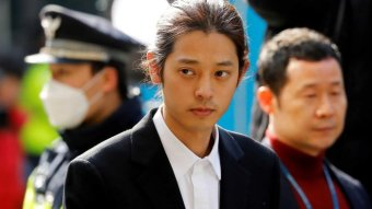 Man-bunned K-Pop star Jung Joon-young arrives for questioning by police.