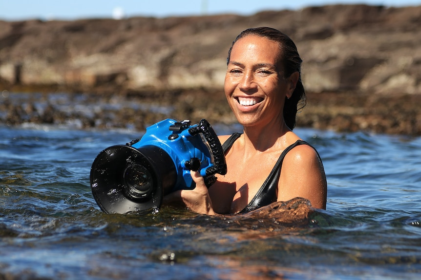 A smiling young woman in the ocean, holding blue underwater housing for her camera.