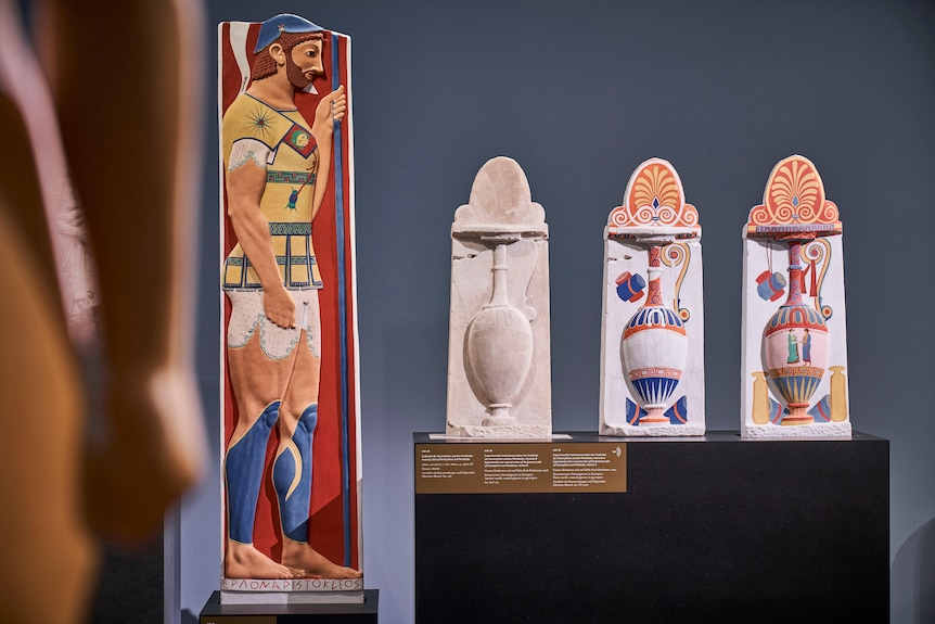 An ancient greek soldier in profile and painted in vivid colours, three identical Greek vases with increasing colours painted on