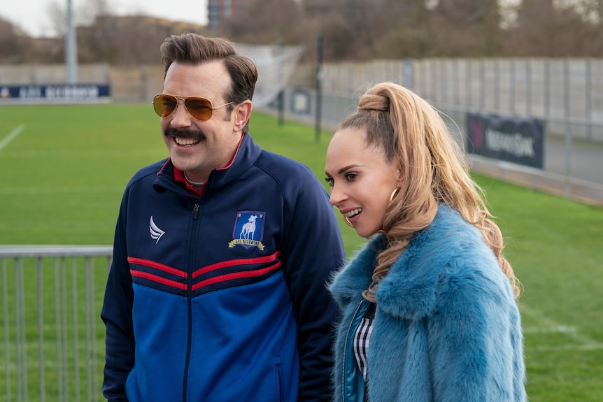 A moustachioed 40-something soccer coach and a 30-something woman with a high ponytail stand together on a soccer field