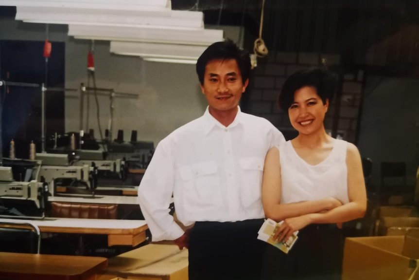 A young man and woman pose together in front of rows of tables with sewing machines inside a garment factory.