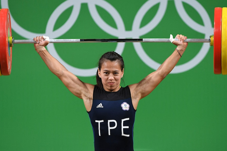 A woman lifts weights at an Olympic event wearing a uniform for Chinese Taipei.