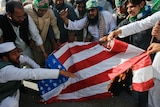 A group of bearded men in traditional Pakistani clothing burn a US flag.