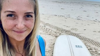 A young women with long blonde hair is smiling while standing on a beach with a surf board on the sand behind her.