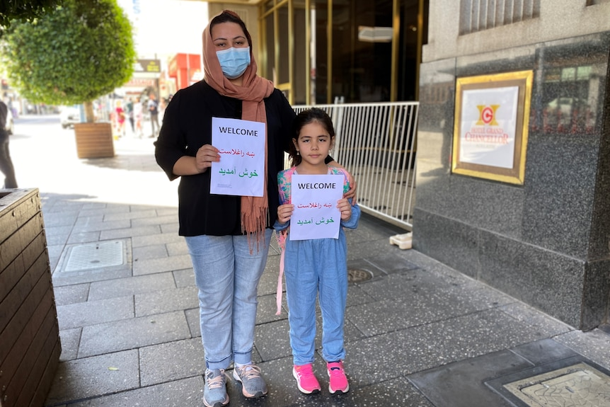 A woman and a girl stand side by side holding a sign that reads 'welcome' in three languages.