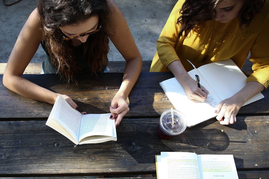 Three students at a table studying together.